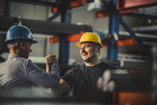 Young happy worker and manager giving each other manly greet at steel mill. Happy metal worker greeting his manager in aluminum mill. happy boss stock pictures, royalty-free photos & images