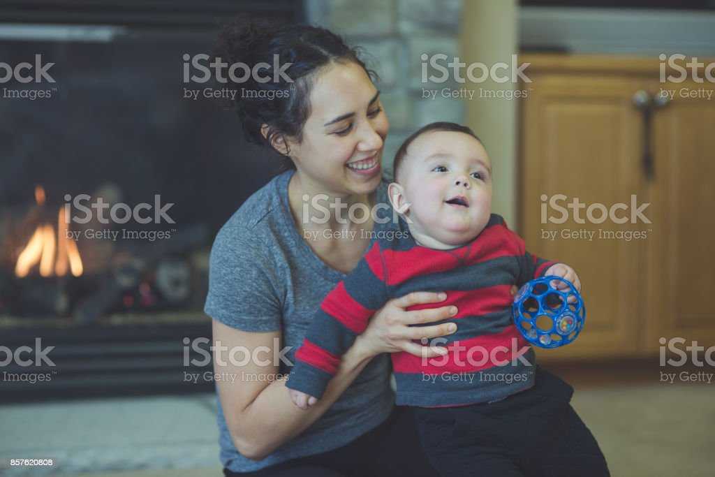 Young Hawaiian mom plays on floor with her six-month old son stock photo
