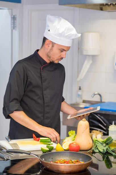 joven jefe de cocina consultar sus recetas en la tableta a través de internet - foto de stock