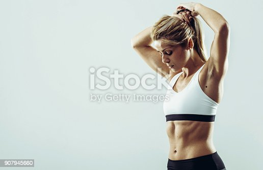 istock Young healthy athlete woman with perfect body posing in front of camera 907945660