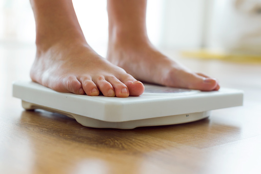 Young Healthy Girl On Home Scales Stock Photo - Download Image Now