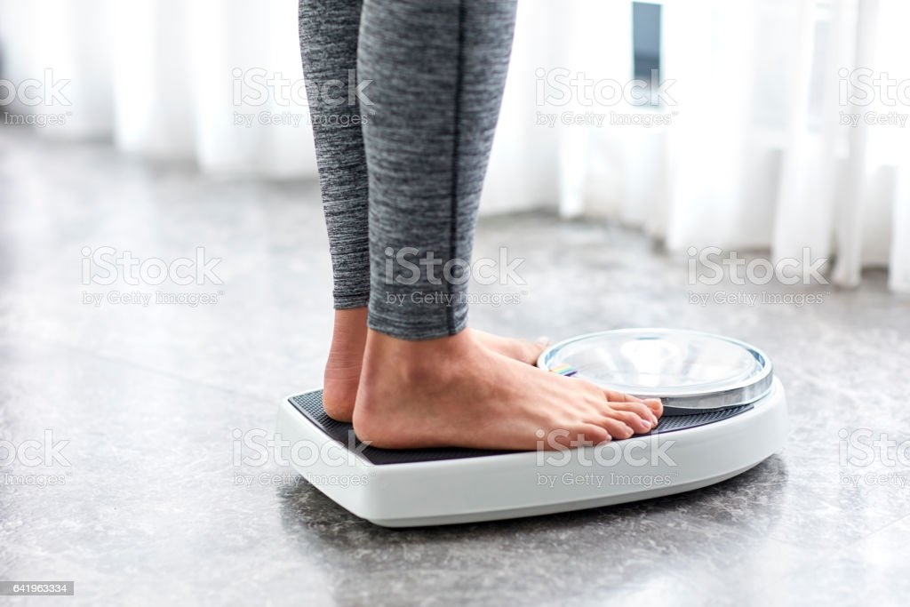 Young healthy girl on home scales royalty-free stock photo