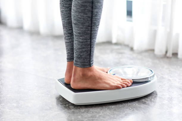 young healthy girl on home scales - weights stock photos and pictures