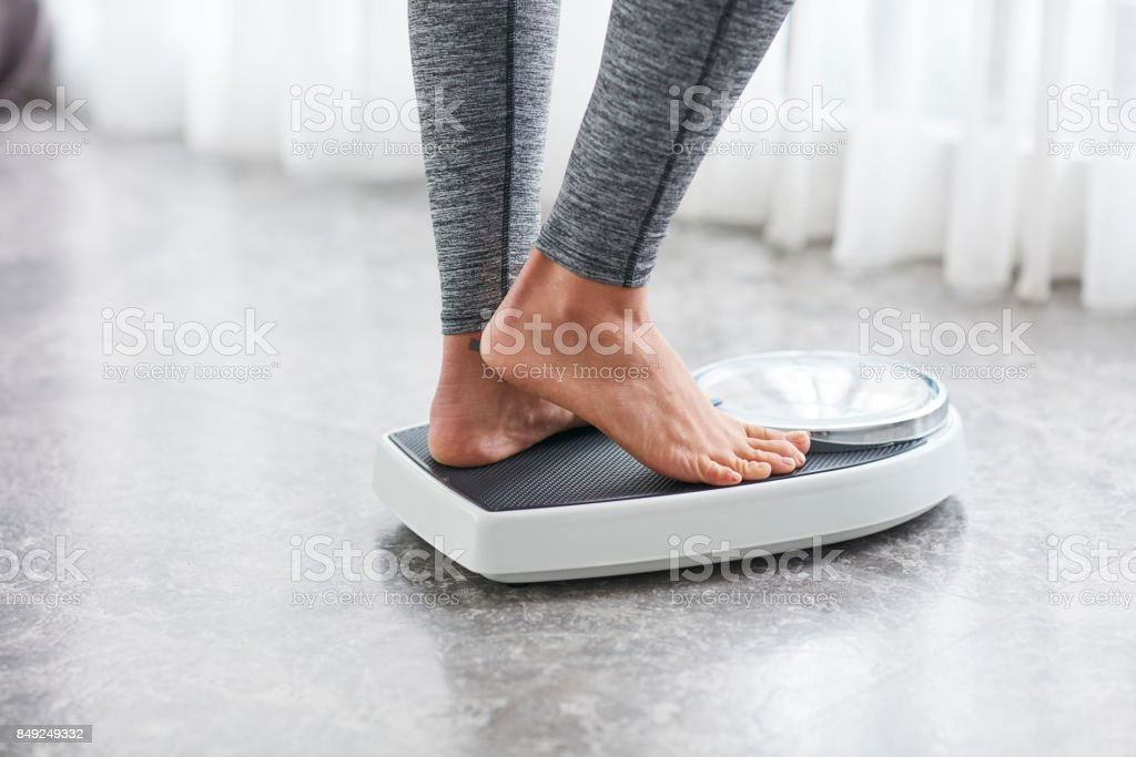 Young healthy girl on home scales - Стоковые фото 20-29 лет роялти-фри
