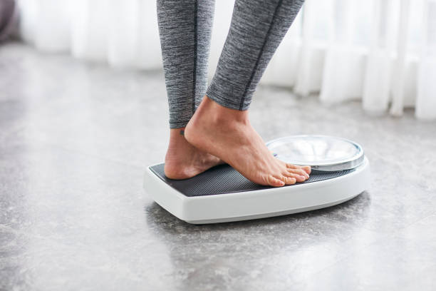 Young healthy girl on home scales stock photo