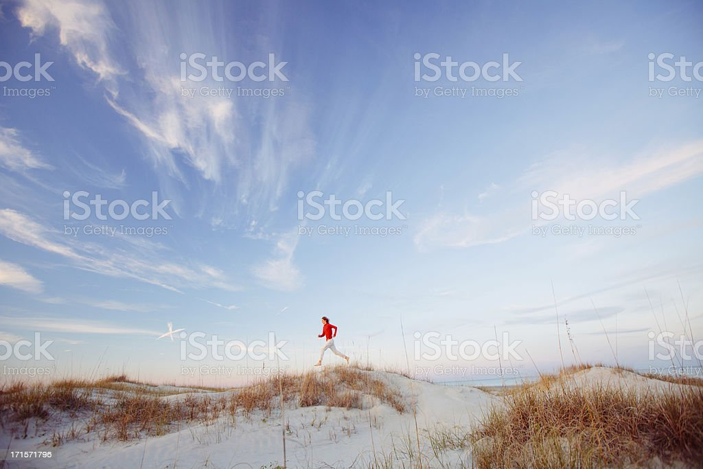 Young healthy man running on the beach stock photo