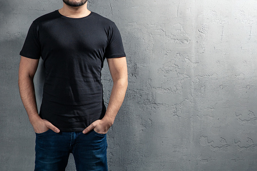 istock Young healthy man with black T-shirt on concrete background with copyspace for your text. Picture without model face. 1124223775