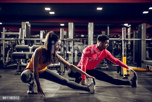 istock Young healthy sporty active shape girl with a ponytail doing leg stretches on the floor while crouching with a handsome helpful personal trainer next to her in the gym. 941192512