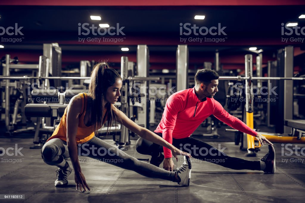 Young healthy sporty active shape girl with a ponytail doing leg stretches on the floor while crouching with a handsome helpful personal trainer next to her in the gym. stock photo