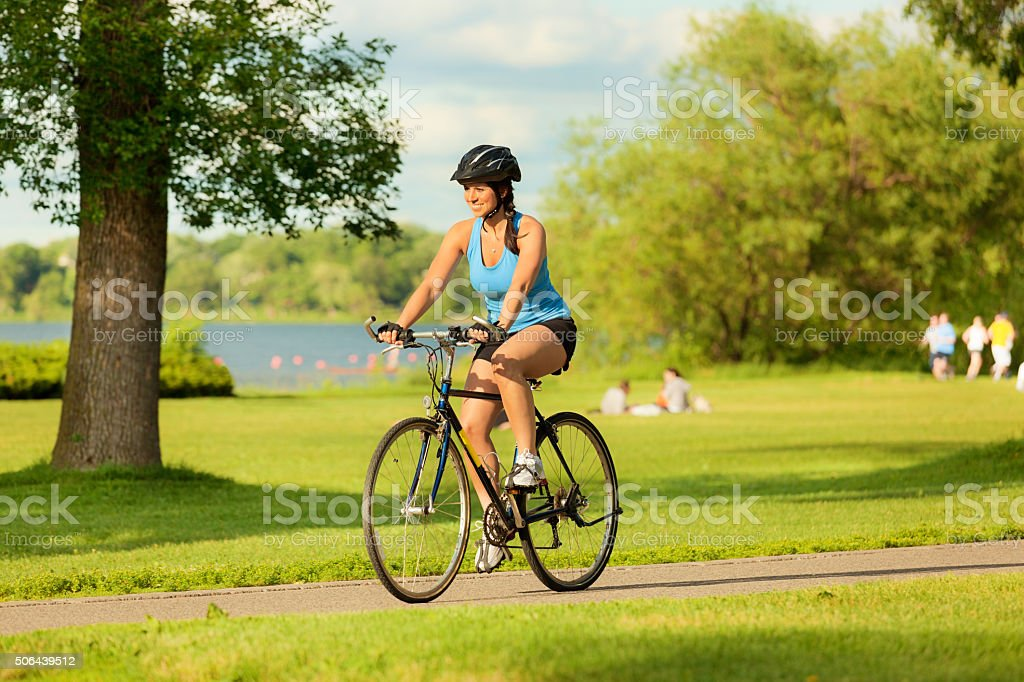 Young Healthy Woman Exercising on Bicycle in Urban City stock photo