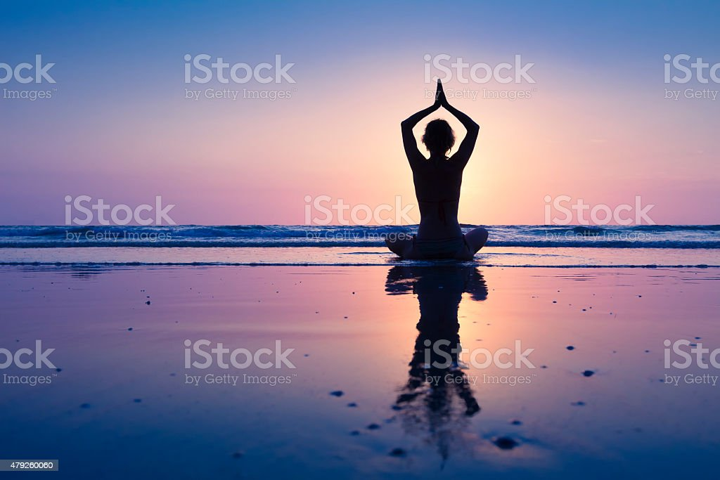 Young healthy woman practicing yoga on the beach stock photo