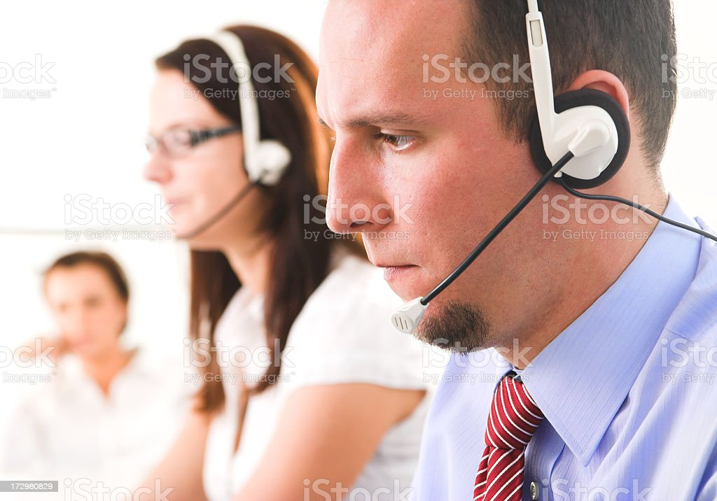 Young help desk operators on headsets royalty-free stock photo