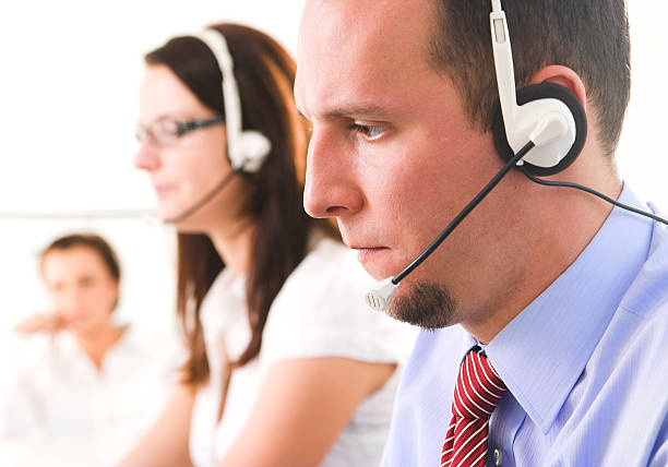 Young help desk operators on headsets stock photo