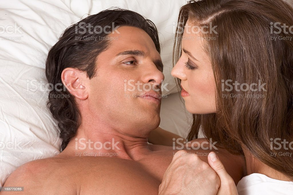 young heterosexual couple in bed royalty-free stock photo