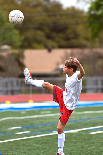 Young teen boy playing soccer. Red and white uniform. Boy in amazing action shots