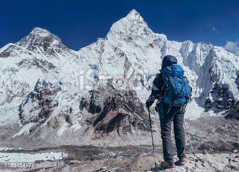 Young hiker backpacker female taking brake in hike walking enjoying Khumbu Glacier. Everest Base Camp route near Gorakshep,Nepal. Everest mount 8848m (left) and Nuptse 7861m (right) on background.