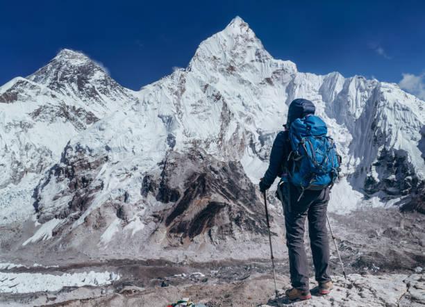 Joven mochilero excursionista hembra tomando freno en la caminata caminando disfrutando del glaciar Khumbu. Ruta del Everest Base Camp cerca de Gorakshep, Nepal. Montura Everest 8848m (izquierda) y Nuptse 7861m (derecha) sobre fondo. - foto de stock