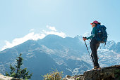 istock Young hiker backpacker female using trekking poles enjoying mountain view during high altitude Acclimatization walk. Everest Base Camp trekking route, Nepal. Active vacations concept image 1187709033