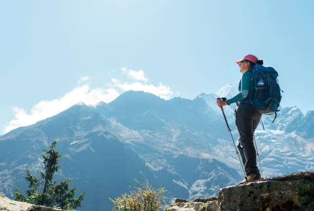 Joven mochilero excursionista hembra usando bastones de trekking disfrutando de la vista de la montaña durante la caminata de aclimatación de gran altitud. Ruta de senderismo Everest Base Camp, Nepal. Imagen del concepto de vacaciones activas - foto de stock