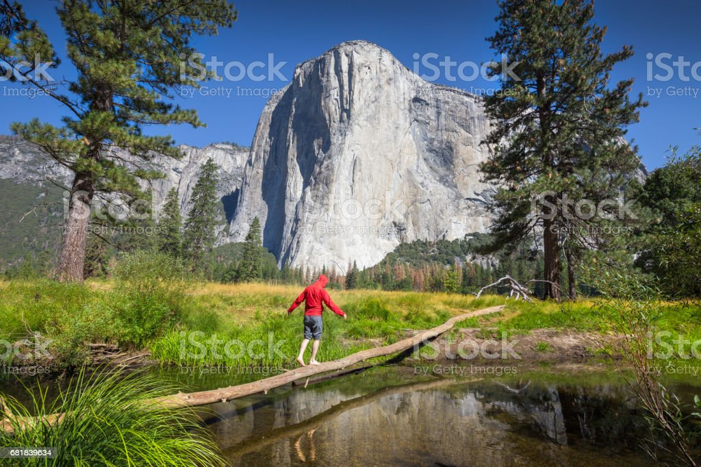 Young hiker balancing on a tree in front of El Capitan, Yosemite National Park, California, USA stock photo