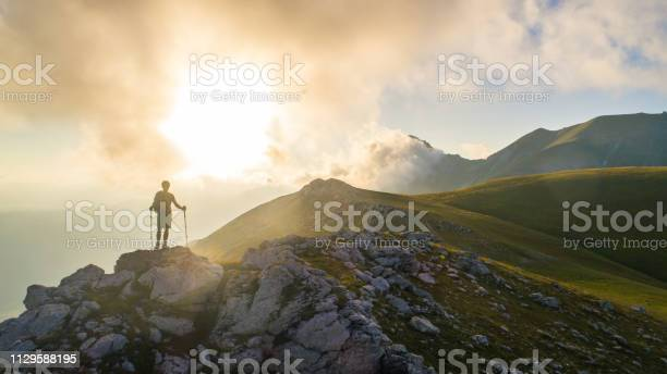Photo of Young hiker man with backpack and walking poles, standing on peak of a mountain looking at sunset in cloudy sky. Green field and rocks. Abruzzo, Italy.