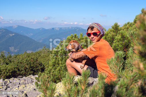 istock Young hiker sits with a dog 611891236