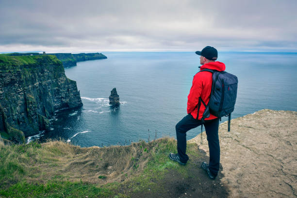 young hiker standing at the cliffs of moher - cliffs of moher stock pictures, royalty-free photos & images