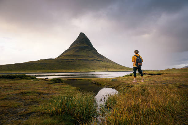 Young hiker with a backpack looks at the Kirkjufell mountain in Iceland stock photo
