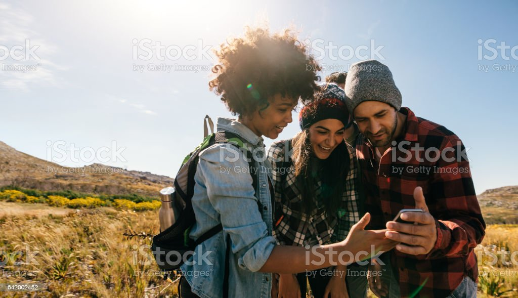 Young hikers looking at pictures on mobile phone – Foto