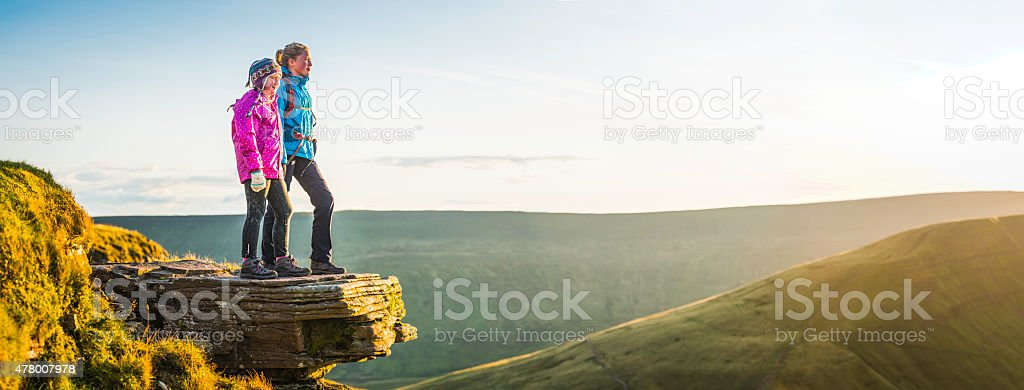 Young hikers on mountain top overlooking golden sunlight landscape panorama stock photo
