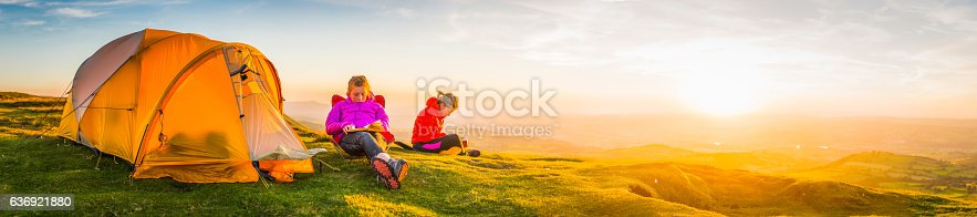 930810564 istock photo Young hikers relaxing on idyllic summer sunset mountain tent camp 636921880