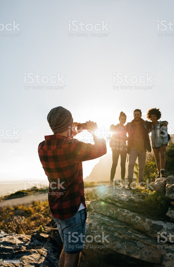 Young hikers taking pictures outdoors stock photo