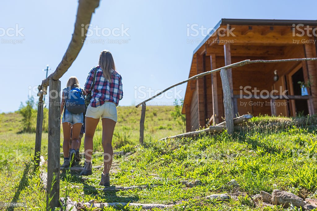 Young hikers walking on trail near cottage stock photo