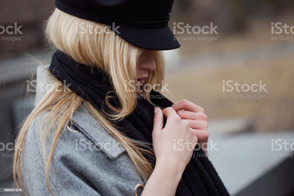Joven, cadera y atractiva rubia paseando por la ciudad, muchacha en un elegante sombrero y un abrigo gris - foto de stock