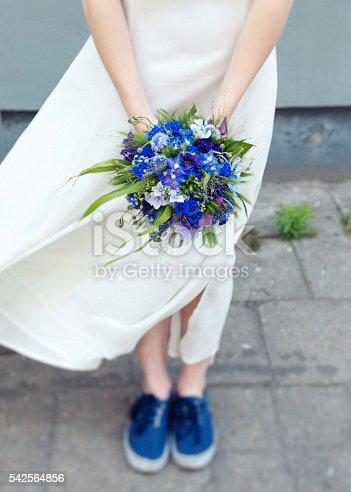 istock Young, hip bride holding bouquet of wildflowers matching her sneakers. 542564856