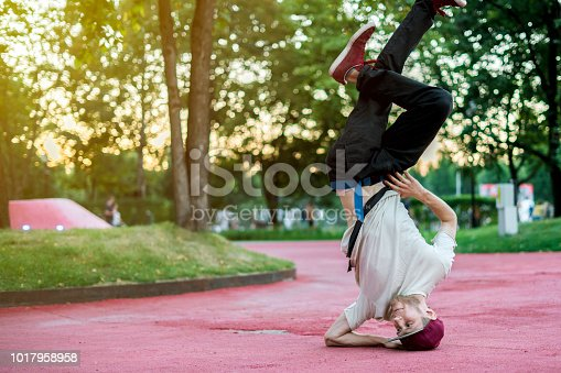 young hip hop street dancer in the city during the dusk doing freeze