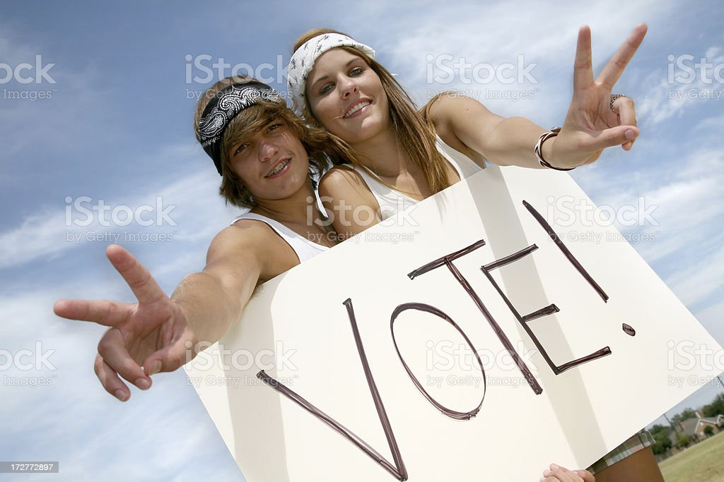 Young Hippie Couple Holding Vote Sign Making Peace Hand Gesture stock photo