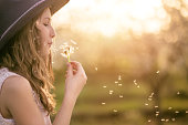 Young girl outside blowing dandelion-copy space