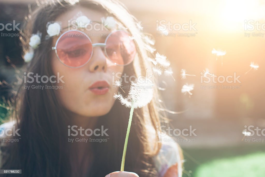 Young hippie woman blowing dandelion outside stock photo