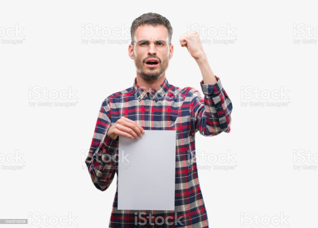 Young hipster adult man holding blank paper sheet annoyed and frustrated shouting with anger, crazy and yelling with raised hand, anger concept stock photo