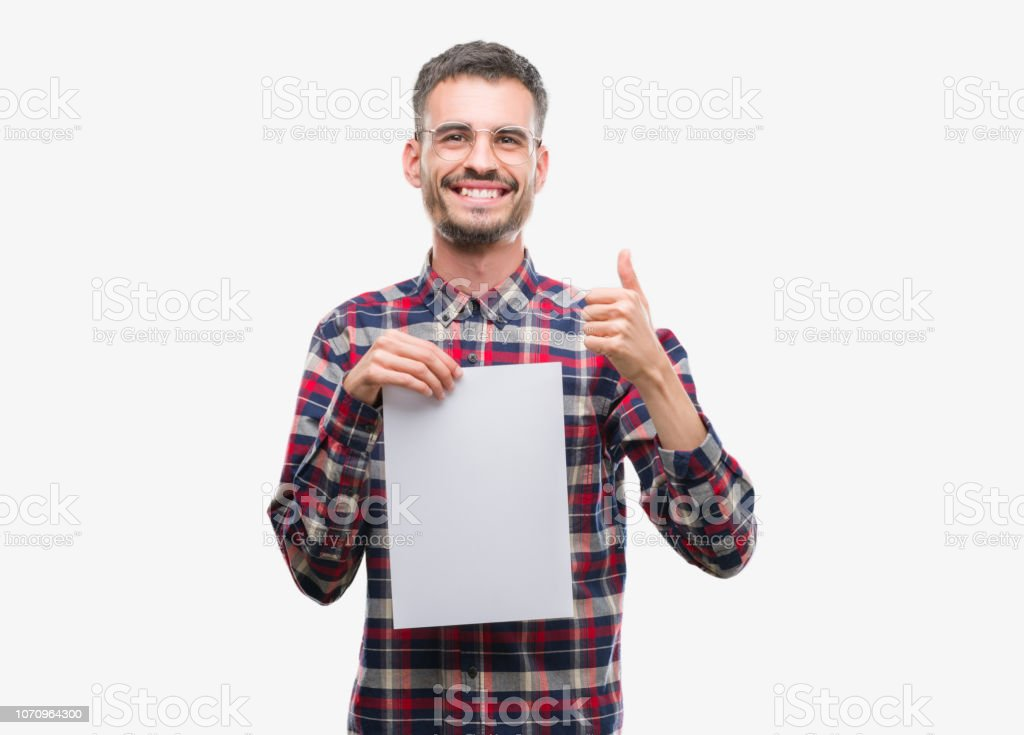 Young hipster adult man holding blank paper sheet happy with big smile doing ok sign, thumb up with fingers, excellent sign stock photo