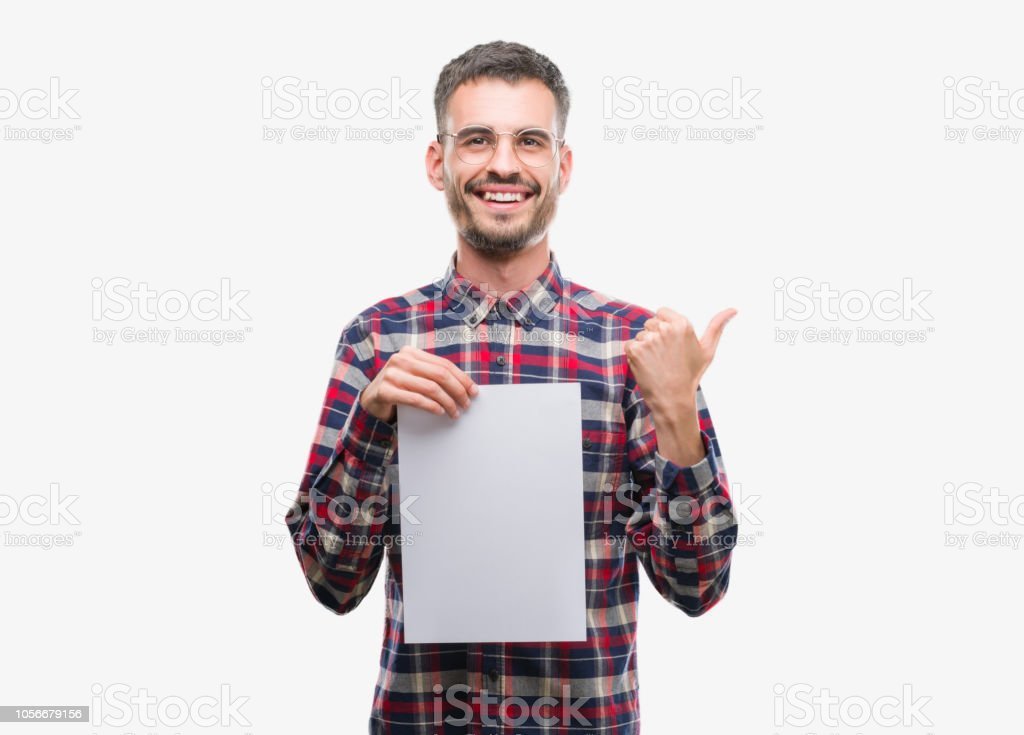Young hipster adult man holding blank paper sheet pointing and showing with thumb up to the side with happy face smiling stock photo