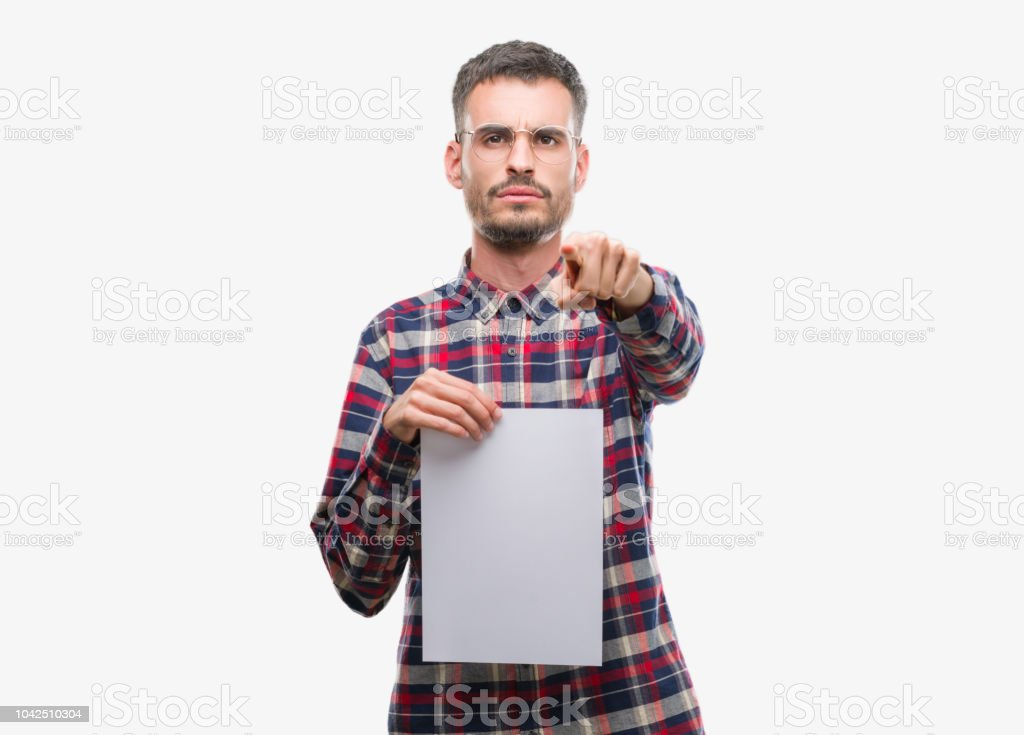 Young hipster adult man holding blank paper sheet pointing with finger to the camera and to you, hand sign, positive and confident gesture from the front stock photo