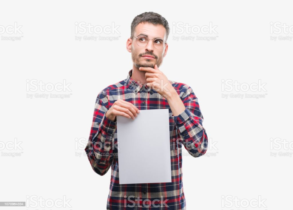 Young hipster adult man holding blank paper sheet serious face thinking about question, very confused idea stock photo
