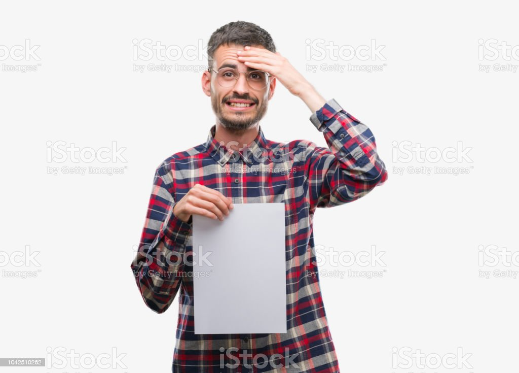 Young hipster adult man holding blank paper sheet stressed with hand on head, shocked with shame and surprise face, angry and frustrated. Fear and upset for mistake. stock photo
