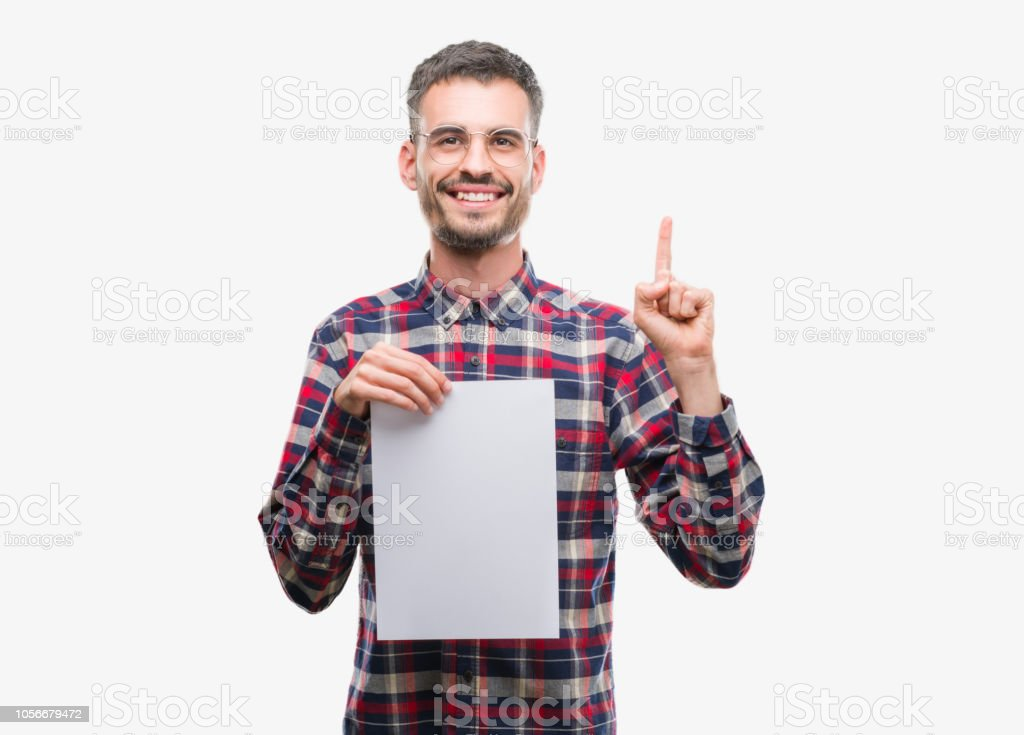 Young hipster adult man holding blank paper sheet surprised with an idea or question pointing finger with happy face, number one stock photo
