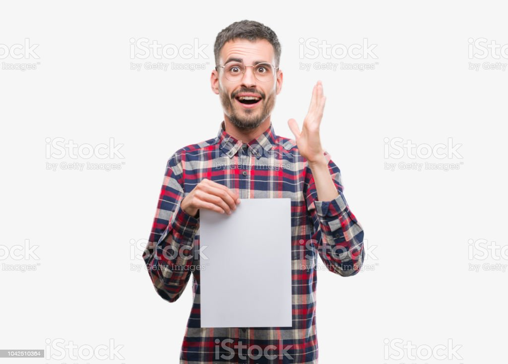 Young hipster adult man holding blank paper sheet very happy and excited, winner expression celebrating victory screaming with big smile and raised hands stock photo