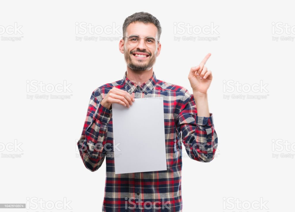 Young hipster adult man holding blank paper sheet very happy pointing with hand and finger to the side stock photo