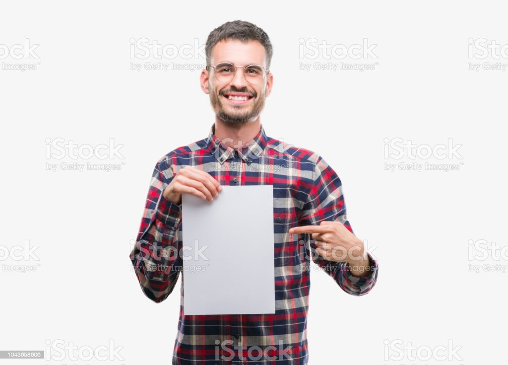 Young hipster adult man holding blank paper sheet very happy pointing with hand and finger stock photo