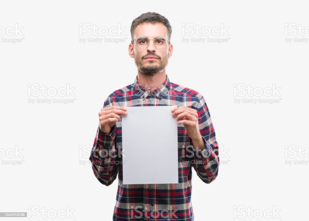Young hipster adult man holding blank paper sheet with a confident expression on smart face thinking serious stock photo